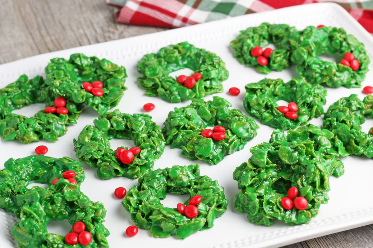 angle view of cornflake wreath cookies on a white serving platter