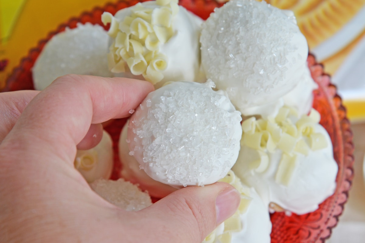 hand picking up a white chocolate oreo cookie ball