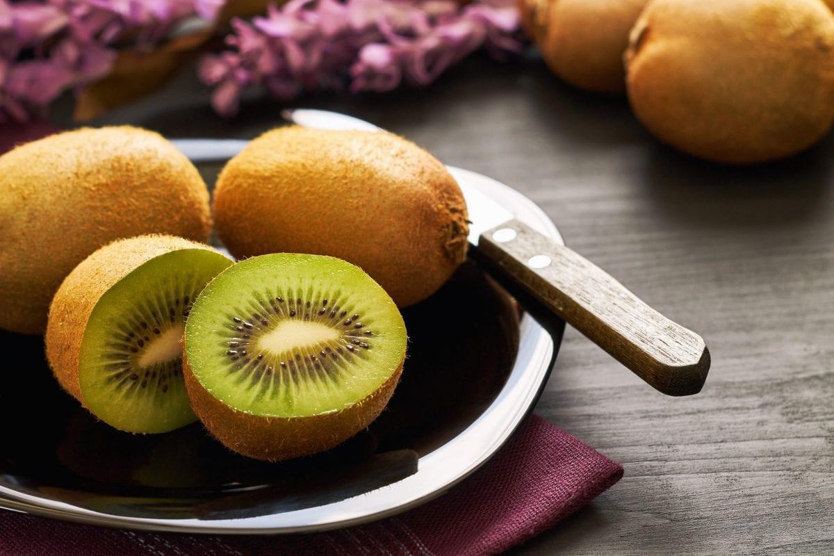 cut and whole kiwi on a plate