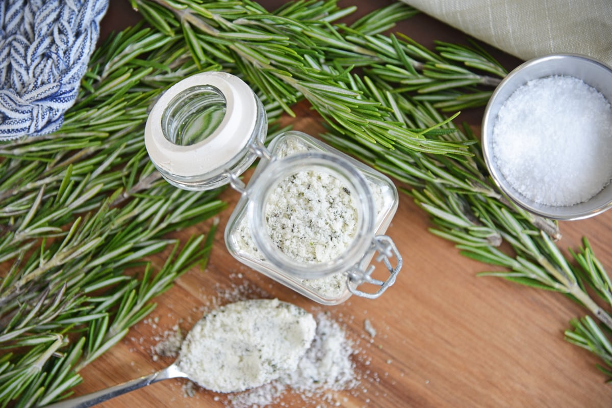 overhead of rosemary salt in a glass jar with a spoon