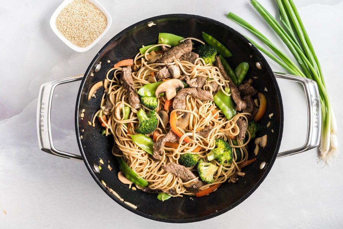lo mein in a wok before garnishing