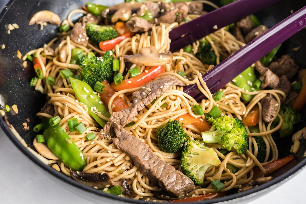 tongs in a skillet of beef lo mein