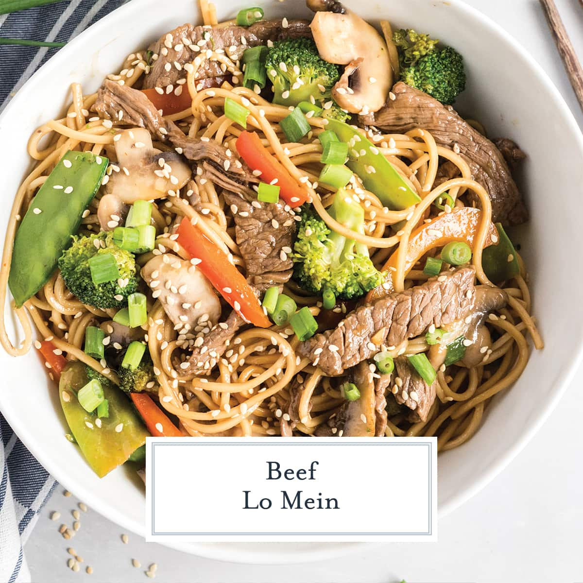 white bowl of lo mein garnished with scallions and sesame seeds