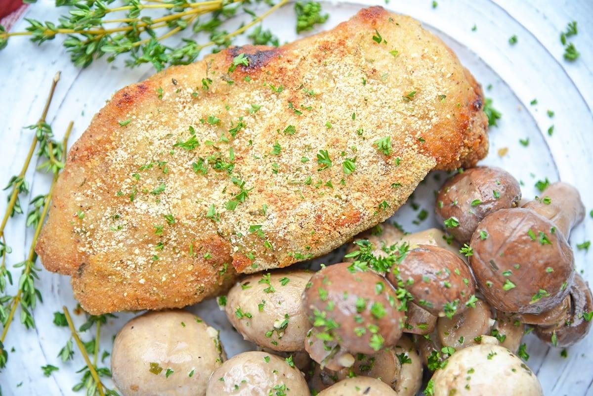 crispy baked pork chop with mushrooms on a plate