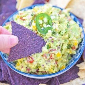 blue corn tortilla chip dipping into guacamole dip