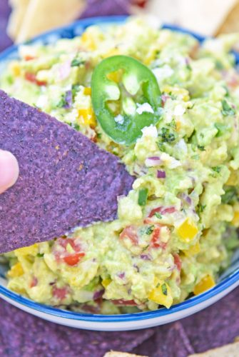 blue corn tortilla chip dipping into guacamole dip
