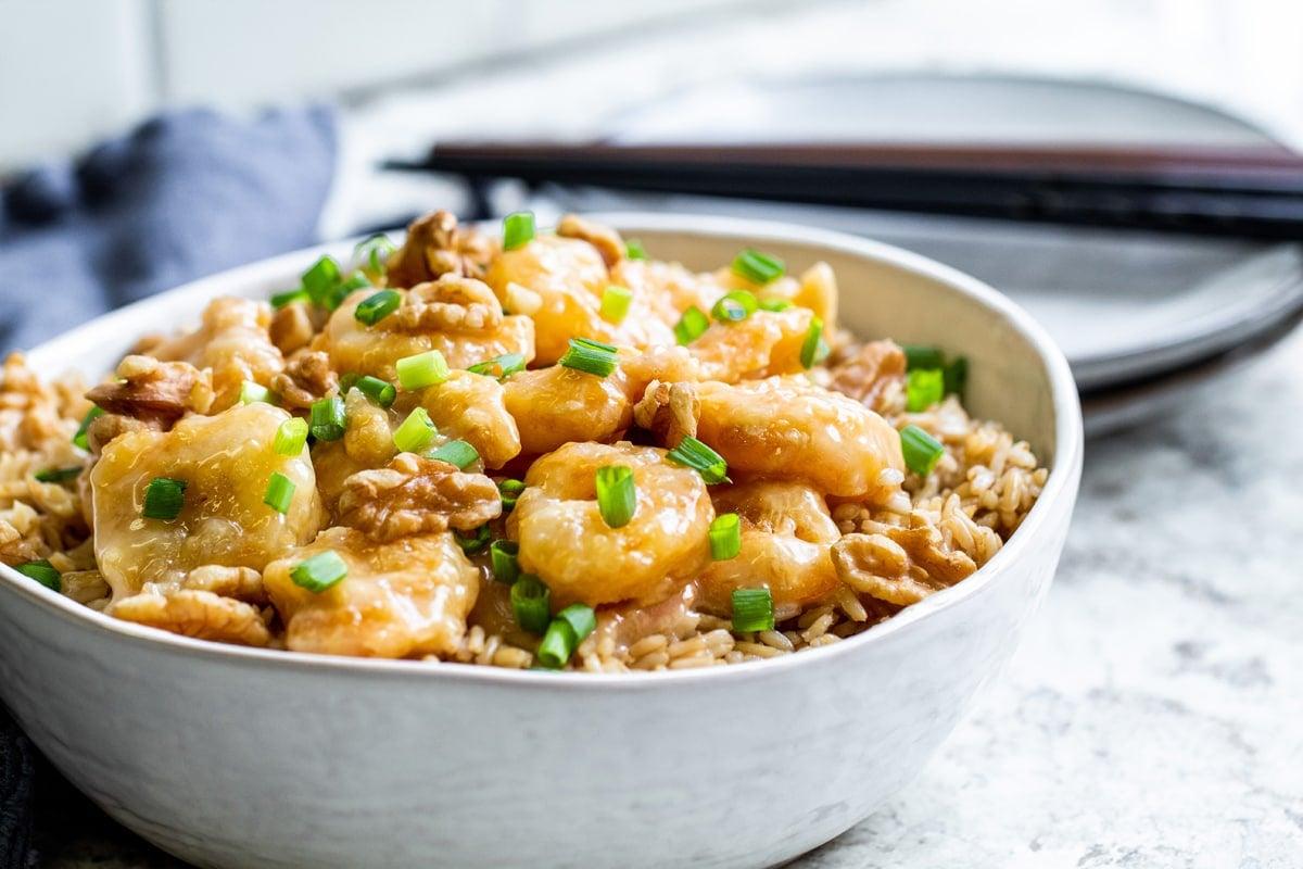 angle view of honey walnut shrimp with scallions