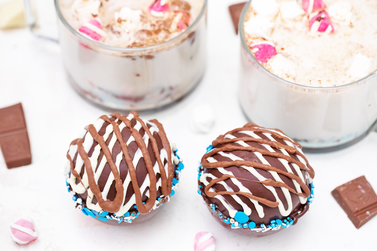 two hot chocolate bombs with blue sprinkles