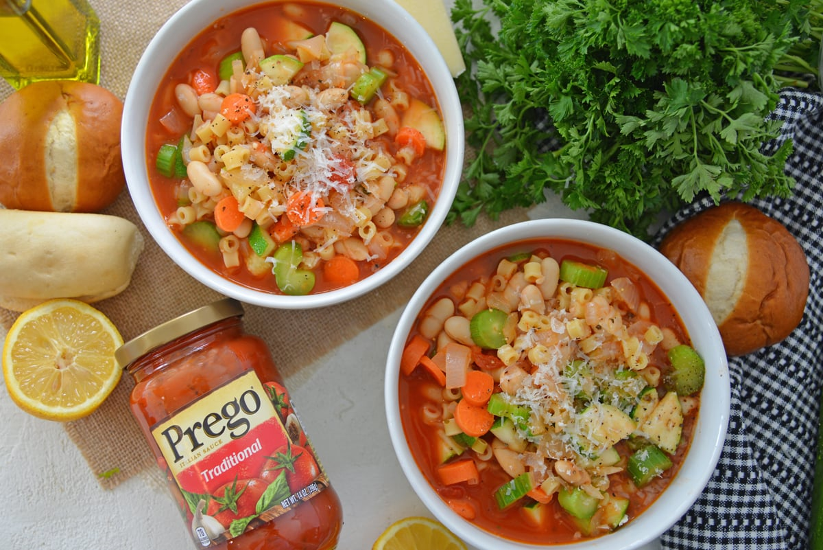 Two bowls of minestrone soup garnished with parmesan cheese