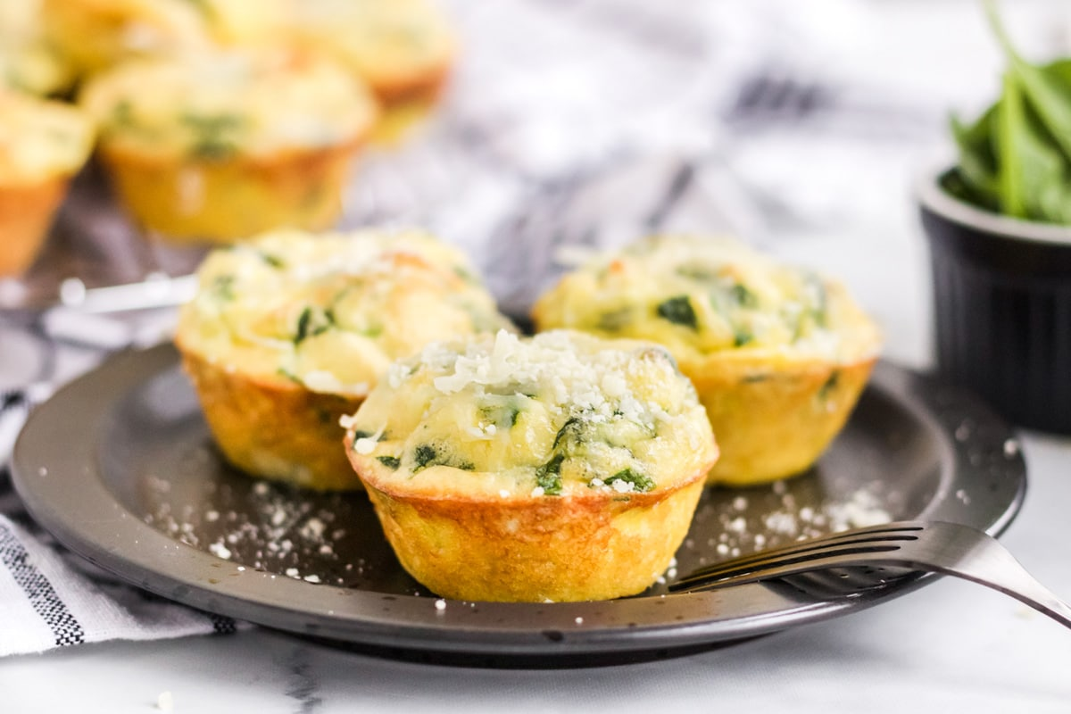 quiche florentine muffins on a black serving plate