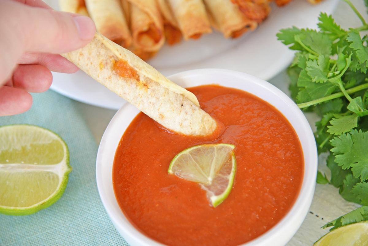 chicken taquito dipping into ranchero sauce