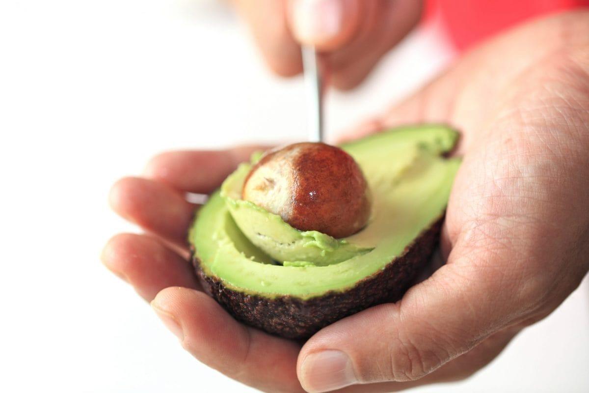 hand pitting an avocado