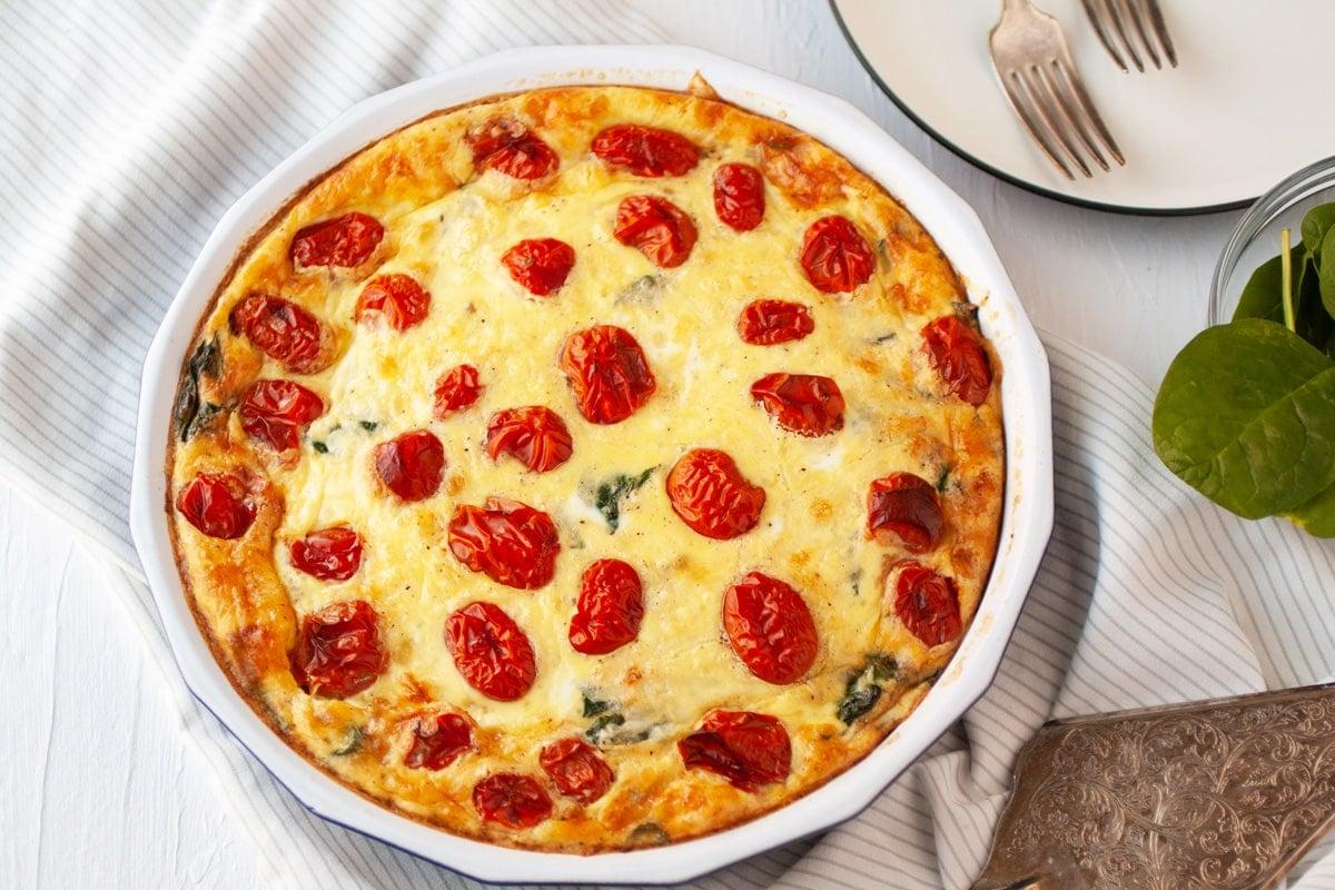 overhead of spinach quiche with tomato