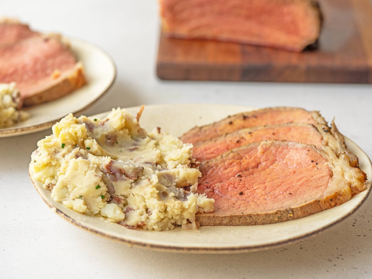 sliced of roast beef on a plate with mashed potatoes