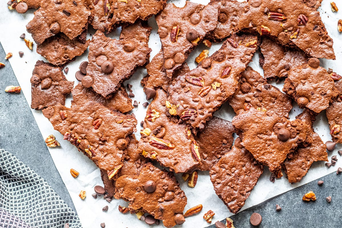 broken pieces of crunchy brownie pieces on parchment with nuts and chocolate chips