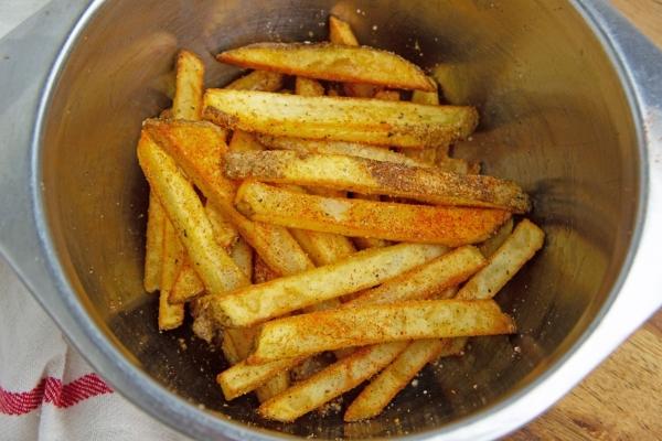 tossing fries in seasoning