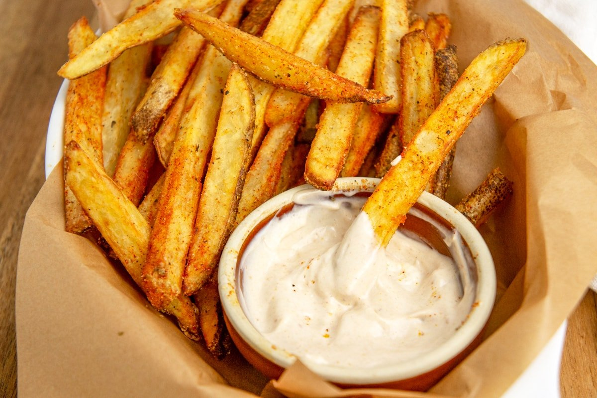 fry dipping into aioli sauce