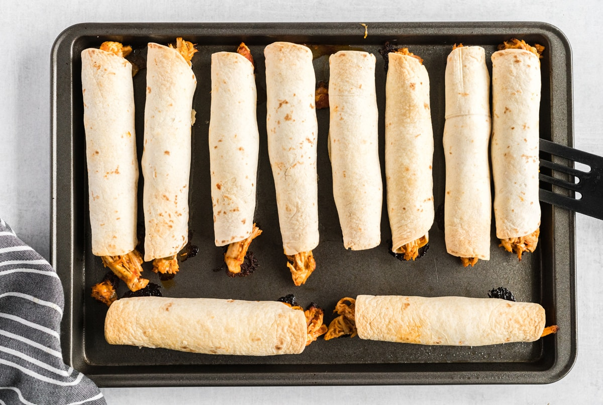crispy baked chicken taquito rolls on a baking sheet