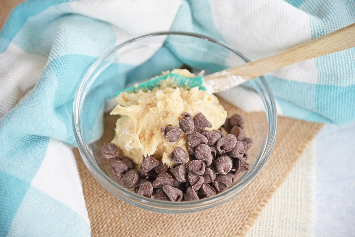 adding chocolate chips to cookie dough