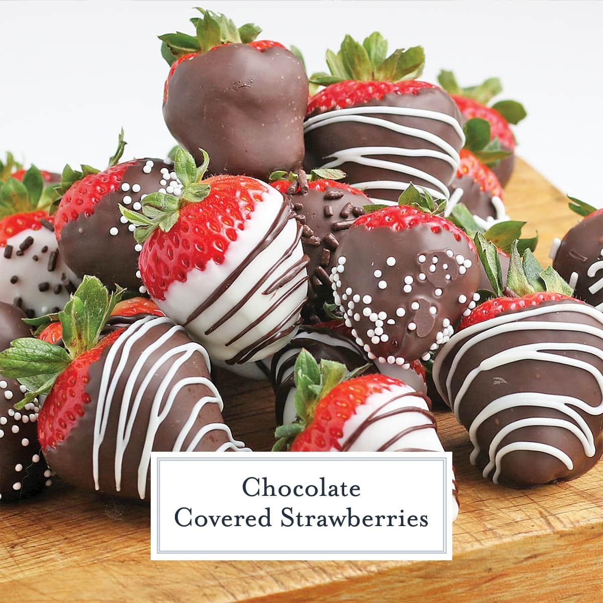 close up of chocolate covered strawberries on a wood cutting board
