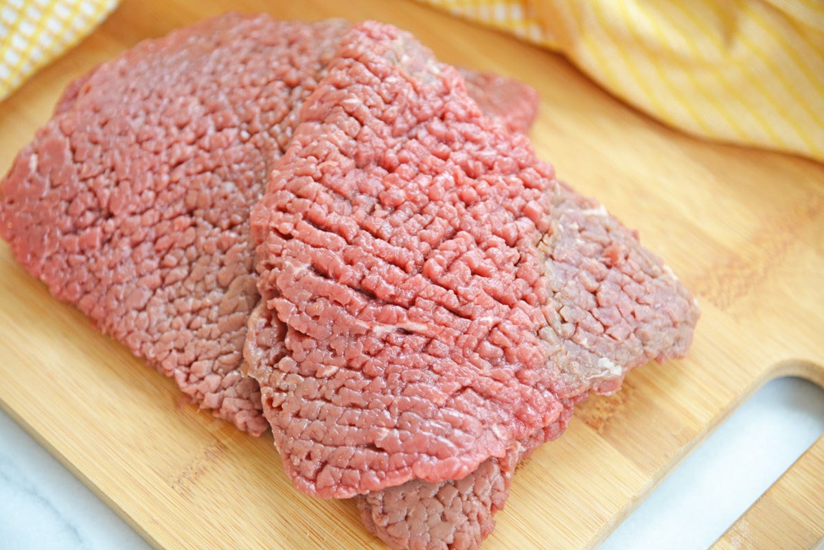 close up of tenderized cube steak on a wood cutting board