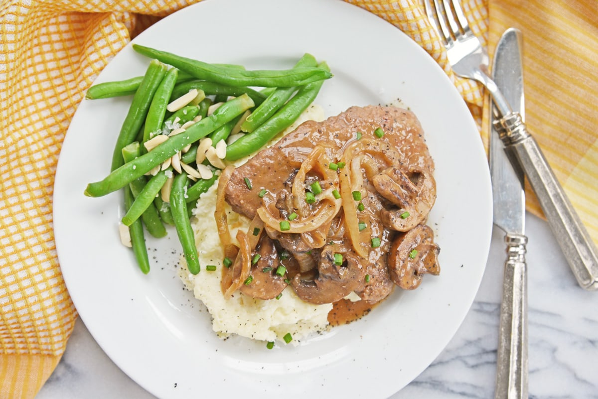 overhead of cube steak with gravy and green beans