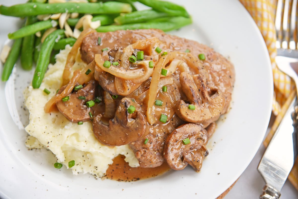 angle view of cube steak with onions and mushrooms gravy and chive garnish