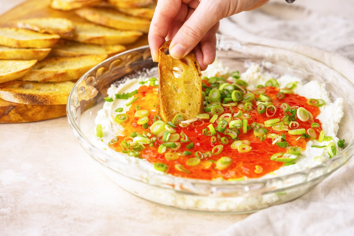 baked goat cheese dip with a buttery crostini dipping in