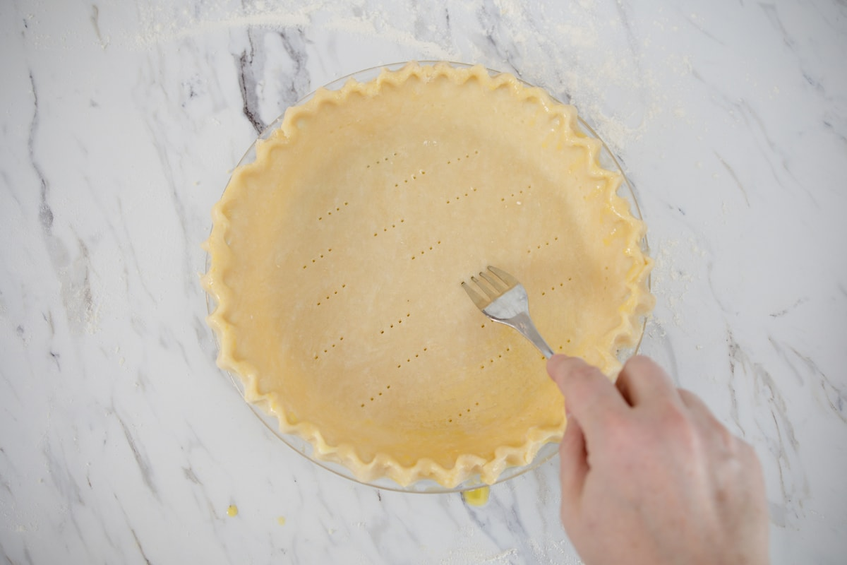 piercing unbaked pie crust with a fork