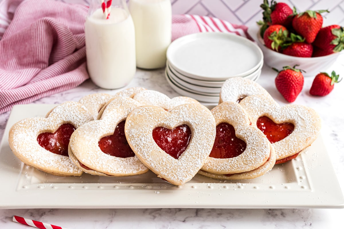 white serving platter of strawberry jam cookies with milk and small white plates