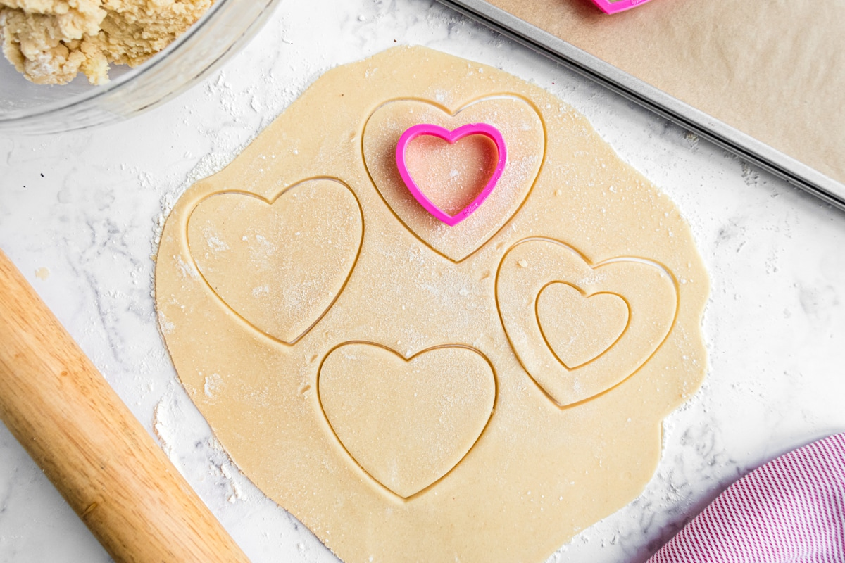 sugar cookie dough rolled out with heart shaped cookie cutters