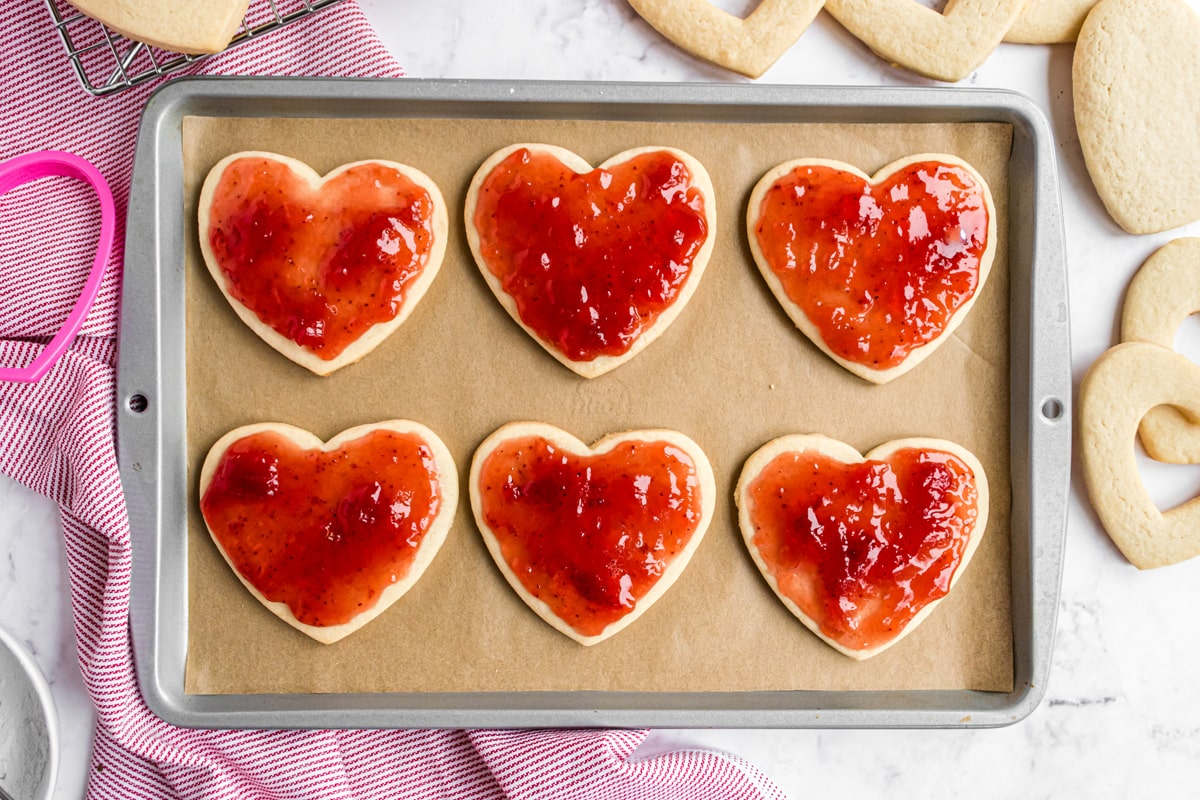 strawberry jam on sugar cookies on a baking sheet