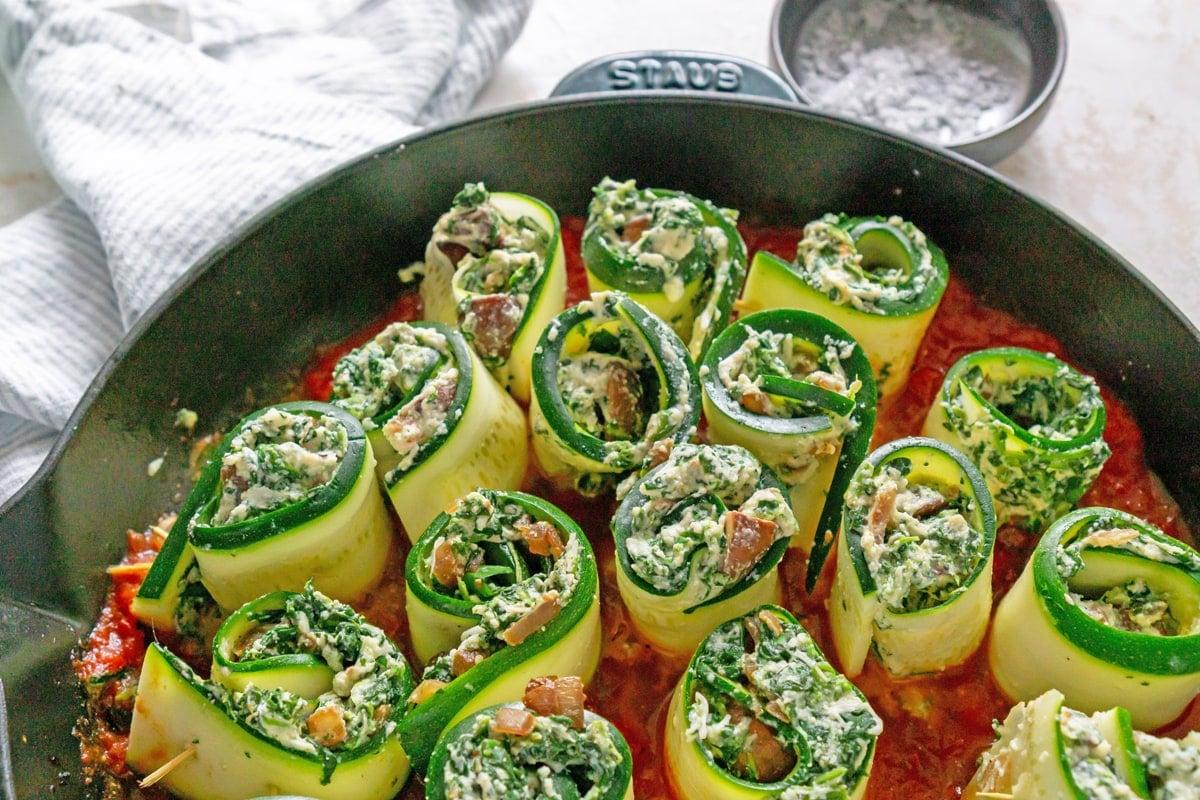 raw zucchini rolls in a marinara sauce in a skillet