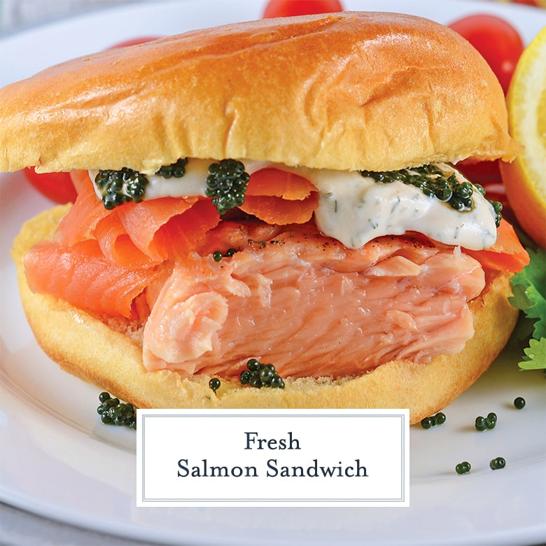 side view of salmon sandwich with fresh salmon, smoked and dilled sour cream on brioche bun