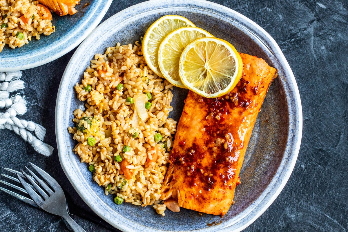 overhead of salmon on a blue plate with fried rice