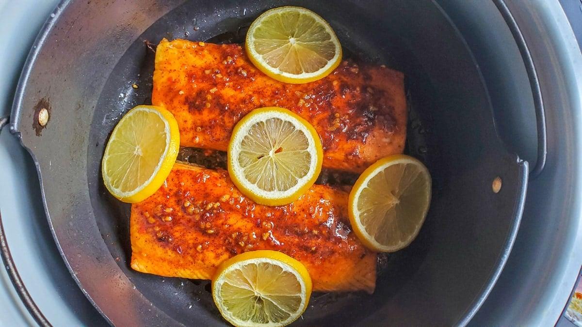 lemon slices over salmon filets in an air fryer basket