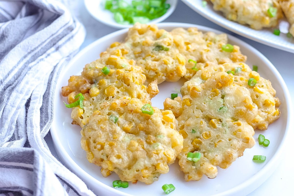 corn fritters on a white plate with scallions garnish