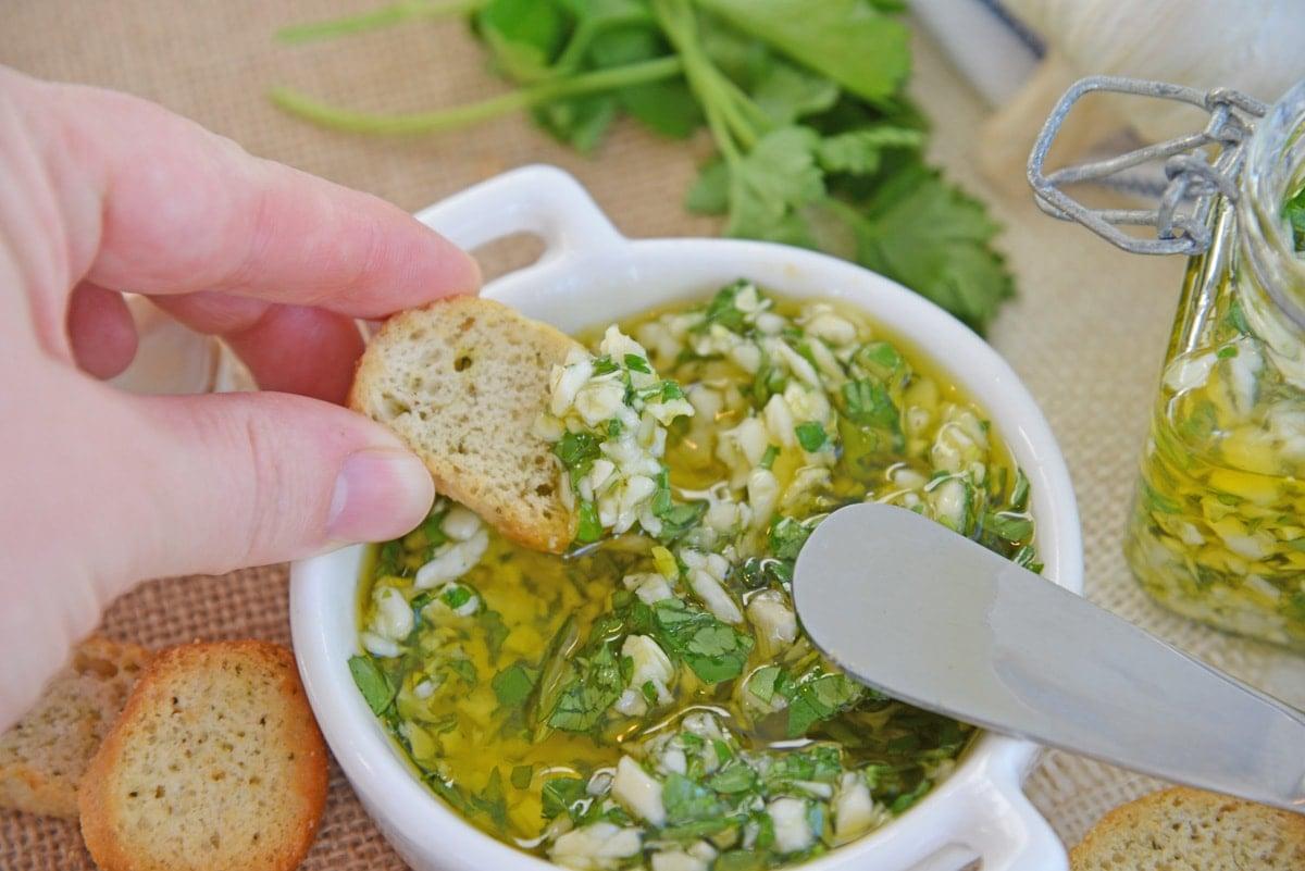 dipping crostini in garlic relish