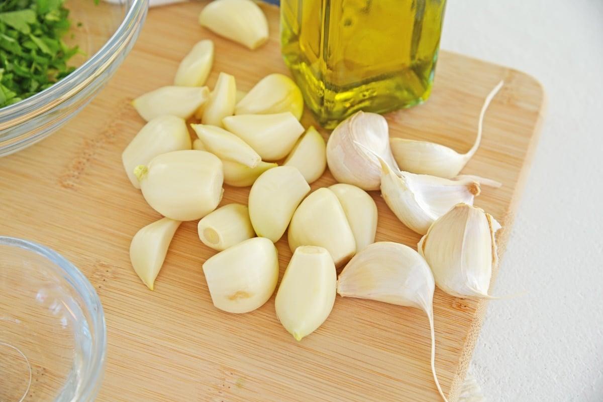 raw garlic cloves on a wood cutting board