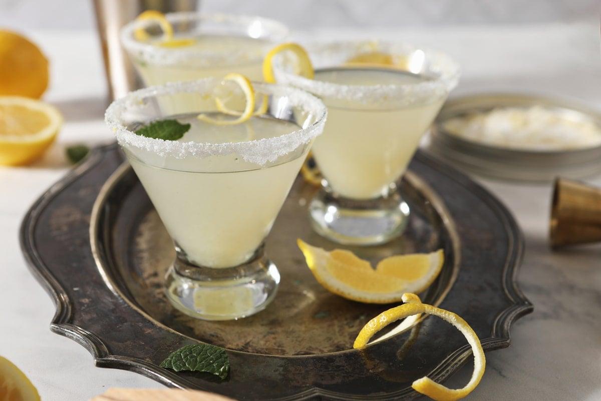 lemon martinis on a tray with lemon garnish