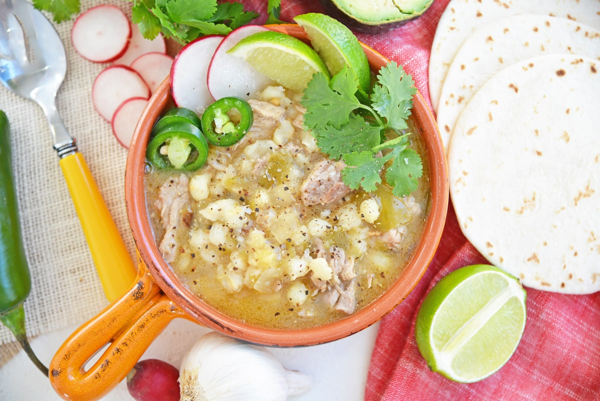 overhead of pork pozole with garnishes