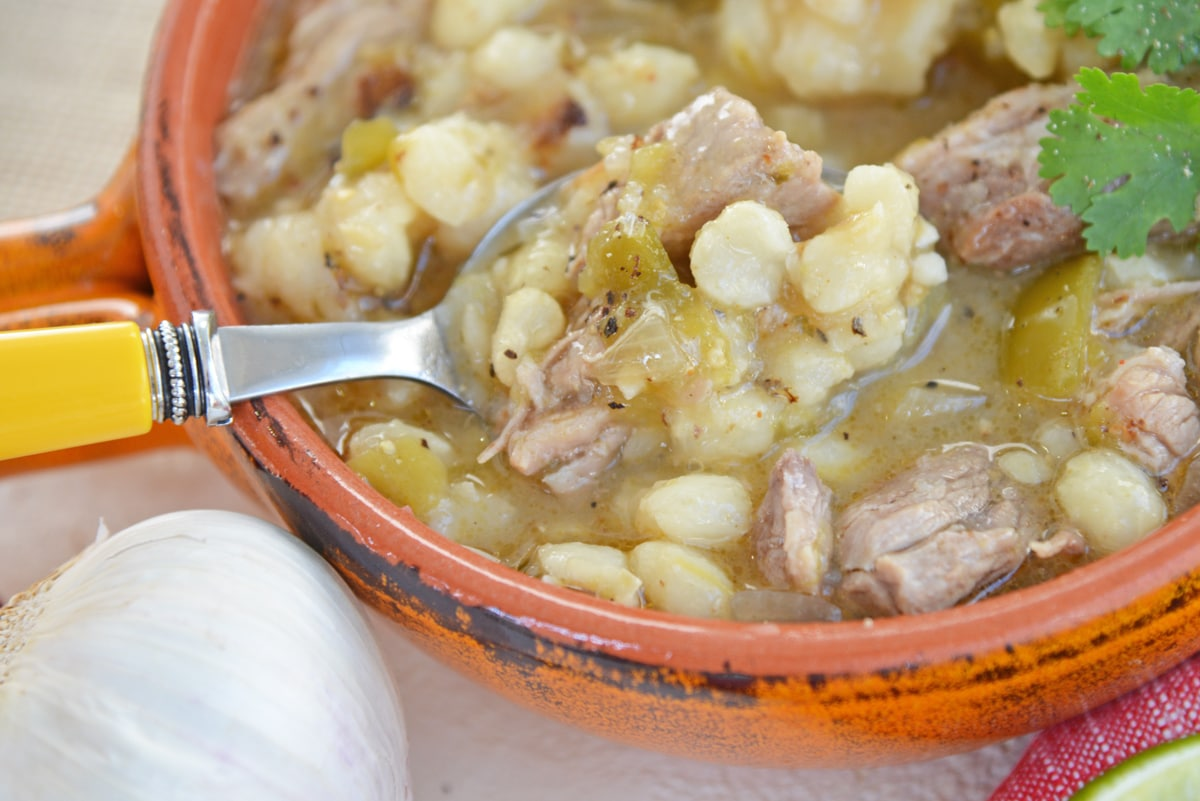 spoon digging into a bowl of pork pozole