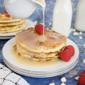 syrup pouring over a stack of raspberry pancakes