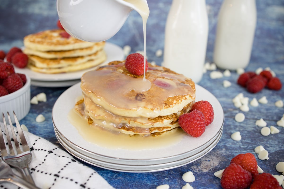 syrup pouring over white chocolate raspberry pancakes