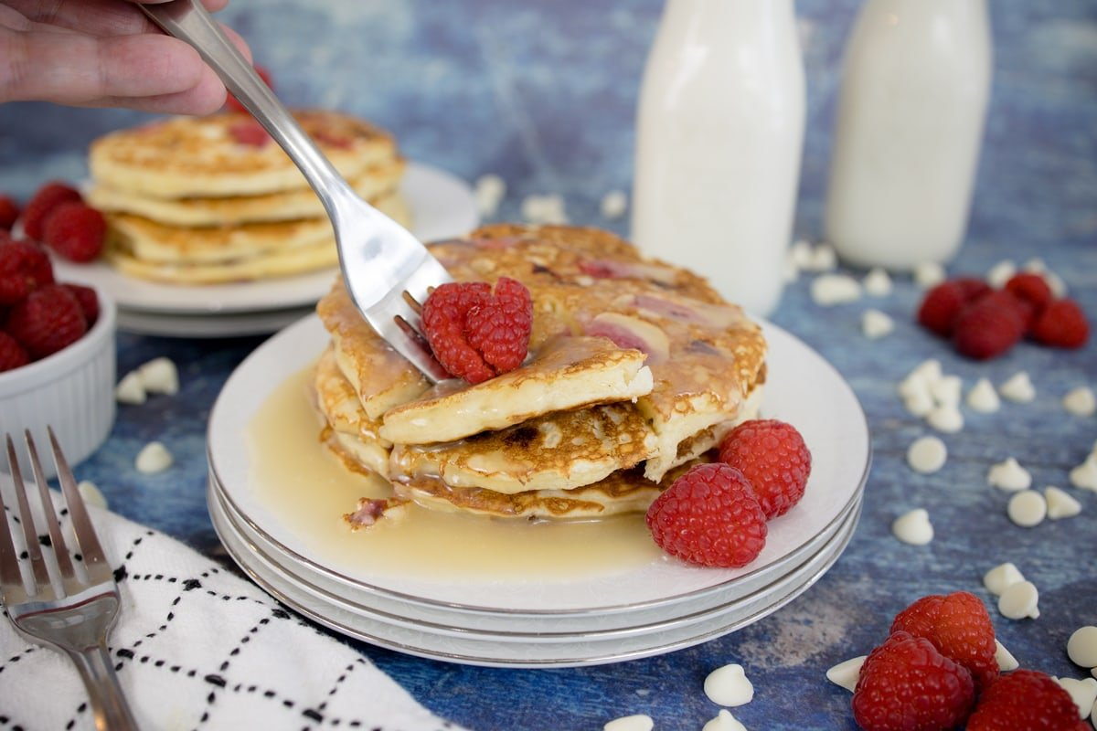 fork digging into raspberry pancakes with syrup