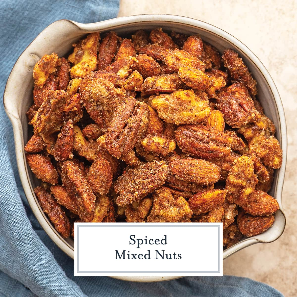 overhead of spiced nuts in a bowl with blue linen