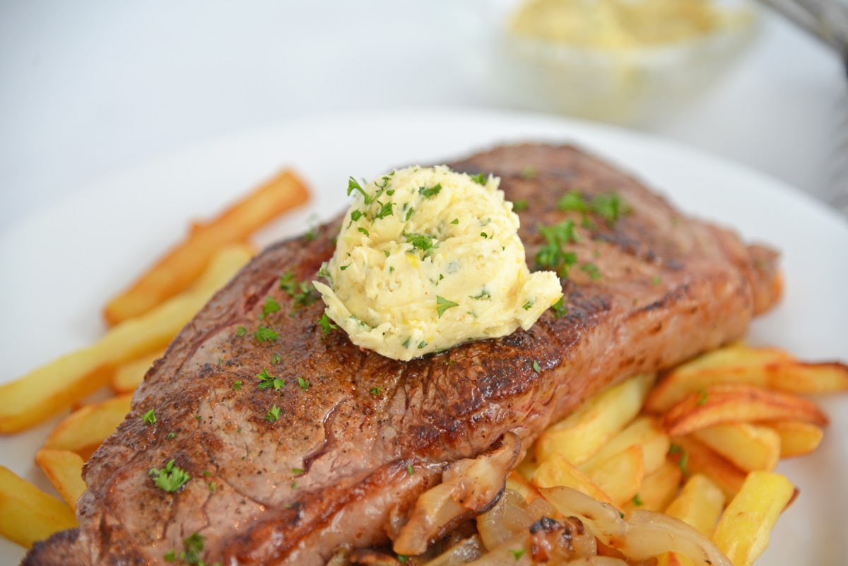 close up of plated steak frites with compound butter