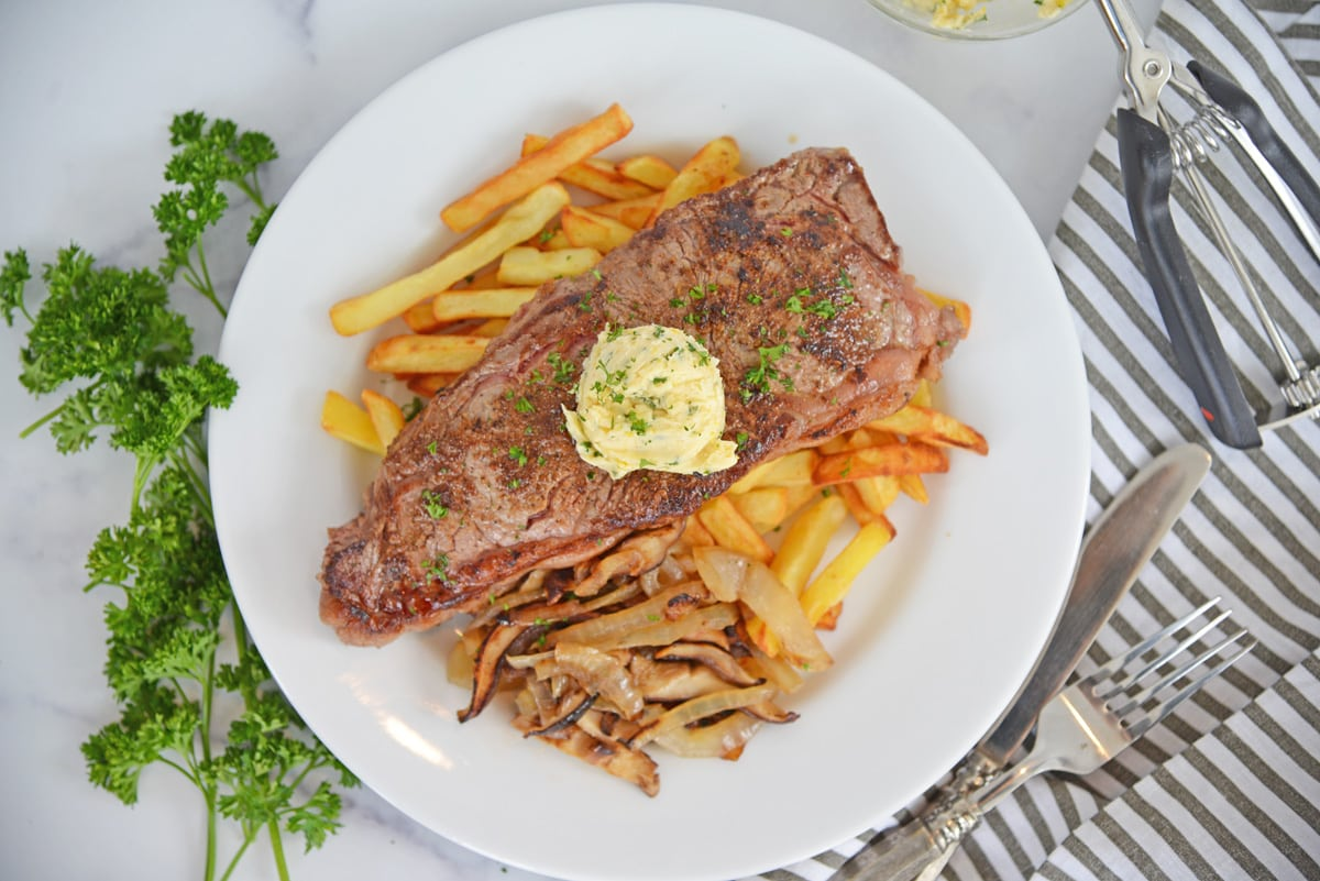 overhead of plated steak frites with butter