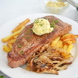 angle view of steak frites with onions and mushrooms