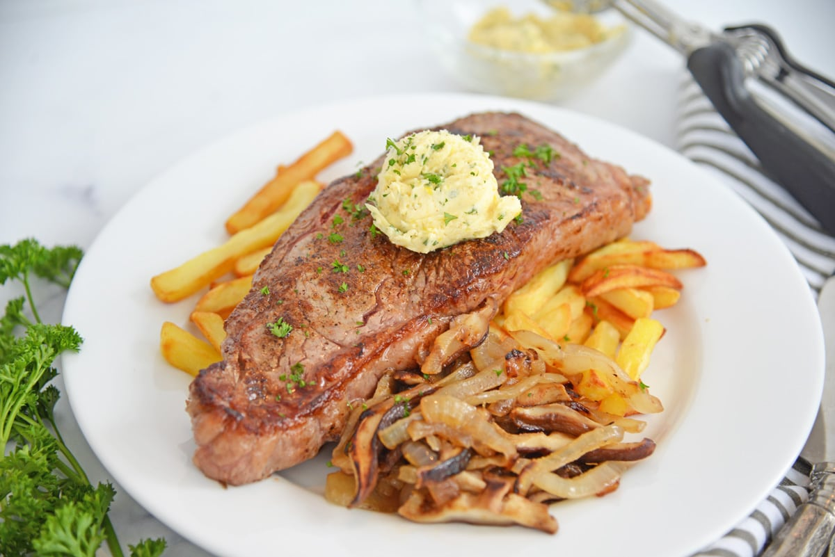 plated steak frites with mushrooms and onions